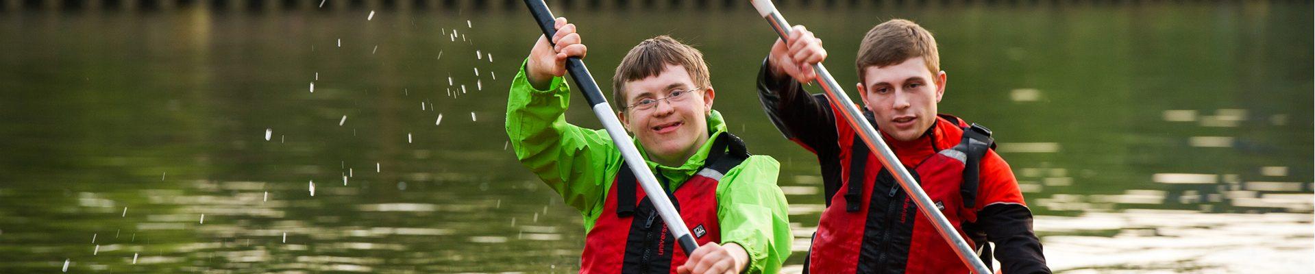 Headerbild Inklusion im Sport: Behinderter und Nicht-Behinderter paddeln gemeinsam in einem Boot