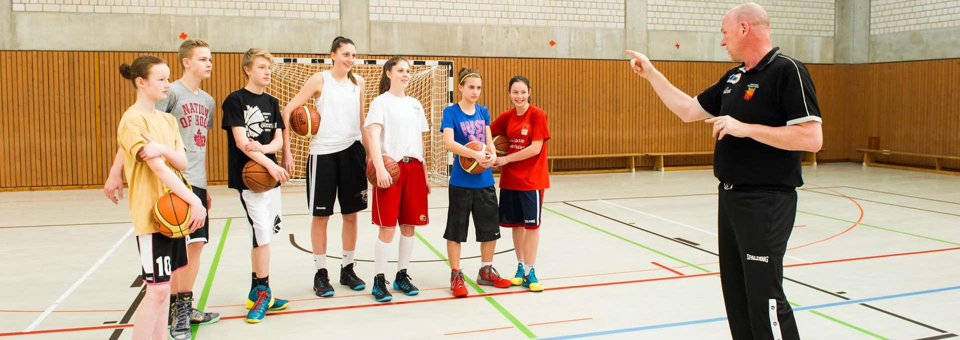 Jugendliche Ballspielgruppe mit Trainer in der Sporthalle