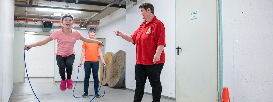Übungsleiterin beim Seilspringen mit zwei Kindenr