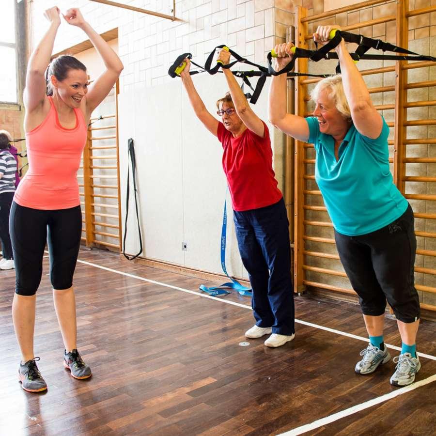 Übungsleiterin in Trainingssituation mit zwei Damen