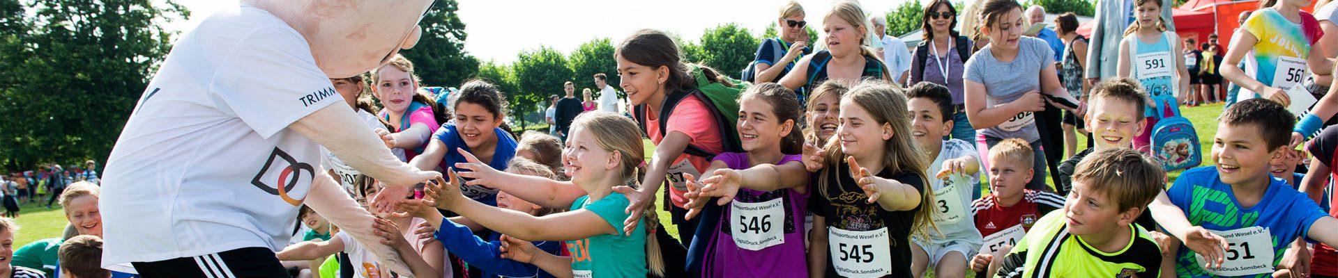 Headerbild Sportabzeichen: Kinder begrüßen beim Sportabzeichen-Tag in Xanten den Trimmy