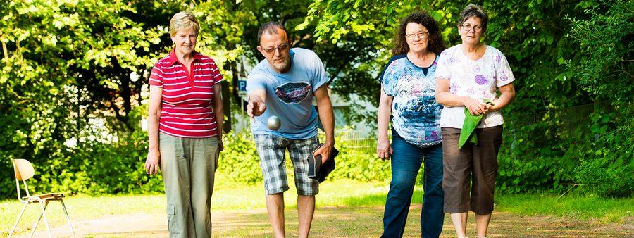 Vier Personen beim Boule spielen
