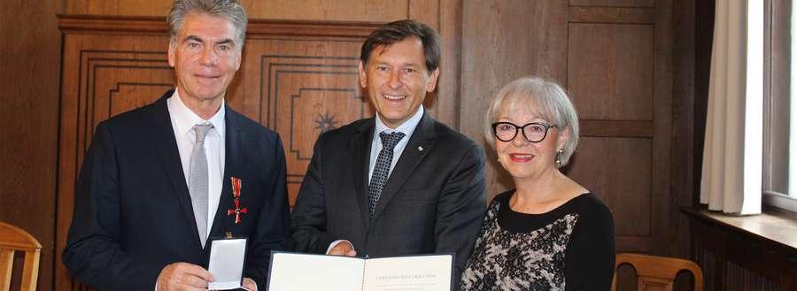 Zwei Männer und eine Frau bei einer Verleihung