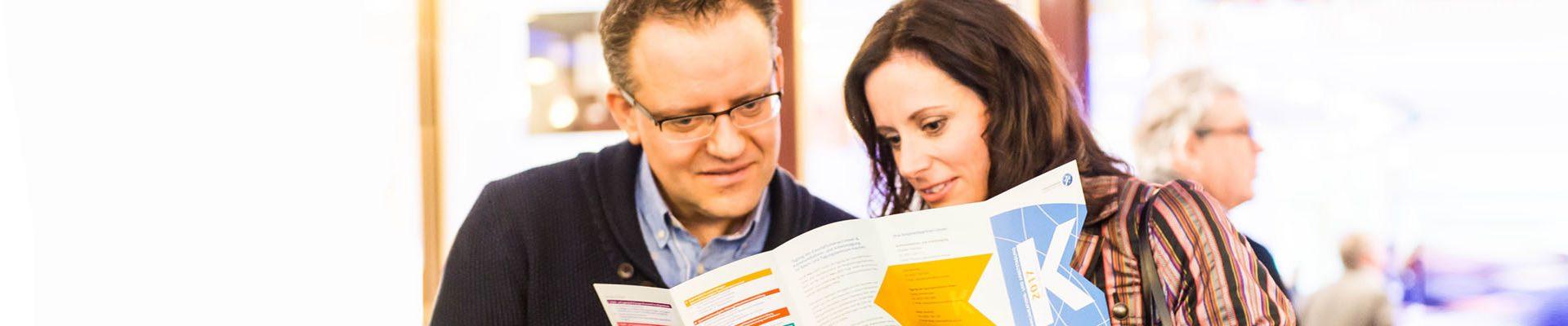 Mann und Frau lesen in einer Broschüre